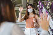 Young Asian woman passenger wearing surgical mask and Waving hand for greeting to her friend in subway train