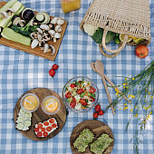 Top view of Picnic basket with healthy vegan sandwiches on blue checkered blanket in park. Fresh fruits, vegetables and orange juise. Vegan picnic concept