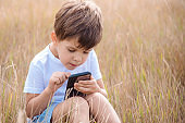 A handsome boy sitting on the grass plays in the phone in the summer game at sunset. The child has fun in nature