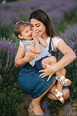 Portrait of young mom with her adorable daughter in summer lavender field. Family denim style. Woman in straw hat. Mom tickle daughter