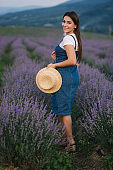 Attractive young woman walking in summer lavender field. Model dressed in denim sundress with straw hat and bag