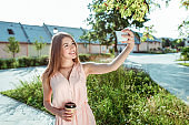 happy girl takes pictures of herself phone, selfie on smartphone, cup coffee tea in hand, pink dress, in summer in city park, grass trees lawn background. Emotions of happiness, joys fun relaxation.