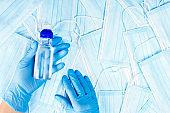 Hand sanitizer bottle in hand with gloves against medical masks background.