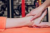 reflexology foot massage, spa foot treatment close-up.