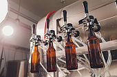 Brewery factory spilling beer into glass bottles on conveyor lines. Industrial work, automated production of food and drinks. Technological work at the factory.