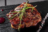 American cuisine. Grilled pork steak, lies on a piece of white bread. Serving food in a restaurant on black slate.