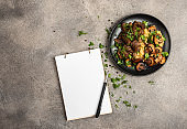 Homemade beef stew with mushrooms and a side dish of lentils on a black plate and notebook for recipes. Top view copy space