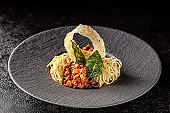 Italian Cuisine. Spaghetti pasta with bolognese sauce, fried cheese and basil chips. Serving dishes in a restaurant in a black ceramic plate. background image, copy space text