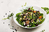 Salad with beetroot, avocado, feta cheese, rucola, tomato, various greens, pumpkin seeds in a white bowl. Diet healthy food for weight loss.