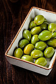 Italian Cuisine. Pickled olives with bone by weight. Serving dishes in a restaurant in a white, rectangular plate. background image, copy space text