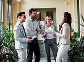Group of smiling business people standing in hallway talking and planning business strategy.
