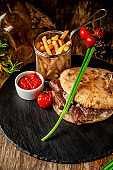 Turkish, oriental cuisine. Turkish tortilla, bun, pita bread with kebab and pickled onions. Serving in a restaurant on a black slate, on wooden table. background image, copy space