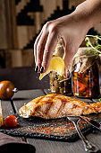 Grilled salmon red fish steak over an open fire. Serving food in a restaurant on black slate.