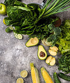 Different vegetables and greens on the grey background.