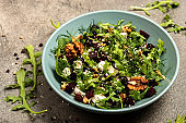 Salad with beets, ruccola, parsley, herbs, feta cheese, walnuts in a bowl. The concept of healthy diet slimming food.