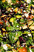 Salad with beetroot, avocado, feta cheese, rucola, tomato, various greens, pumpkin seeds in a white bowl. Diet healthy food for weight loss. Close-up. Top view.
