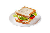 Homemade sandwich made of toast bread, fried egg, melted cheese, tomatoes, cucumber, lettuce, burgers and mayonnaise sauce. Sandwich on a white plate, on a black background.