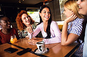 Group of young female friends having fun in cafe, talking and laughing while sitting at table.
