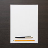Template of white paper with pen and pencil on dark wenge color wooden background
