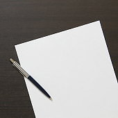 Template of white paper with pen on dark wenge color wooden background