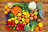 Fresh raw fruit and vegetable on brown wooden table