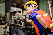 Asian worker working hard in industrial factories suffer from back waist pain while working on machines.
