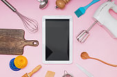 Tools for baking and cooking tablet with blank screen and place for text or image on pink background