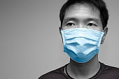 Asian chinese man wearing face mask or disposable protective face shield cloth cover studio head shot with space for text.