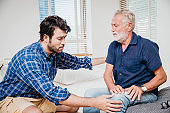 Young men health care elderly uncle in the home, old man pain at knee leg.