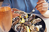 Woman eating fresh oysters with lemon