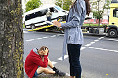 An agent fills out documents after car accident, driver sits nearby and holds his head with his hands