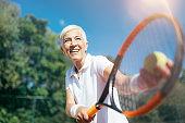 Senior Tennis – Pretty Mature Woman Serving Ball in Tennis