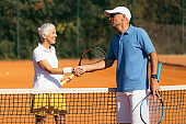 Tennis Instructor with Senior Woman in her 60s Handshaking after Having a Tennis Lesson on Clay Court.