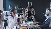 Beautiful young 20s African female boss leading multiethnic business team at office meeting in coronavirus face shields.