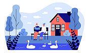 Senior couple watching swans on pond