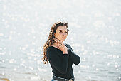 Closeup of a girl with long curly hair against a sunny water of lake.
