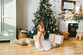 Christmas portrait of beautiful smiling little girl sitting on floor with presents under the christmas tree.