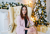 Young brunette woman is sitting in the room next to the Christmas tree
