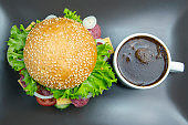 Hamburger with vegetables and sausage and coffee on a gray background. Fast food and breakfast. Calories and diet.
