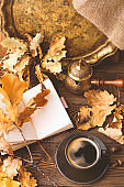Diary, autumn oak leaves and Turkish coffee pot on a wooden background. Copy space. Cozy. Autumn concept