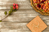 Vintage tray with petals of dried rose flowers, gift box wrapped in kraft paper on a gray table. Flat styling. Copy space for text.