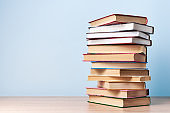 A tall, chaotic stack of books stands on a wooden table against a light blue wall, space for text