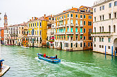 Boats and water taxis sailing and docked on Grand Canal along colorful Venetian architecture buildings in Venice city, Italy