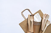 Paper bag with a picnic set: plate, fork, glass, napkins. Caring for the environment.Flatly.