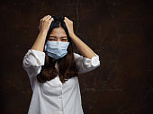 Girl in a surgical mask with a headache. That protects against the spread the flu and pollution.