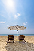 Wooden sunbeds and umbrella on the golden sand of a paradise beach