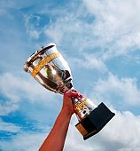 The winner takes it all. Champion winner trophy cup on sky background.