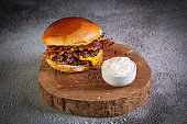 Two smash burgers with cheddar cheese, bacon and garlic sauce. Rustic craft burger.