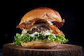 Two smash burgers with cheese, bacon, letuce and garlic sauce. Rustic craft burger.