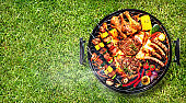 Top view of assorted delicious grilled meat with vegetables on barbecue grill with smoke
